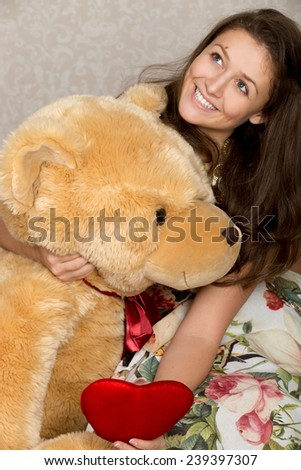 Girl with dreamy expression holds stuffed heart and giant bear - stock photo