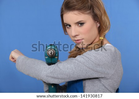 Girl with drill on blue background - stock photo