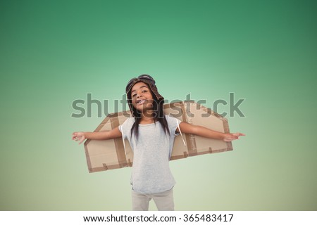 Girl with fake wings pretending to be pilot against blue sky - stock photo
