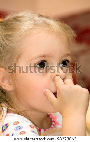 Girl with finger in his nose - stock photo