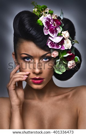 Girl with flowers in her hair on the gray background - stock photo
