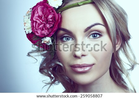girl with flowers on a blue  background - stock photo