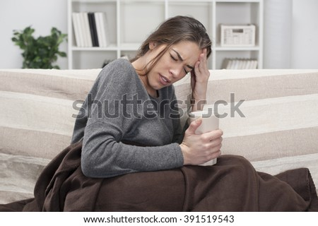 Girl with flu sitting on the bed in the room - stock photo