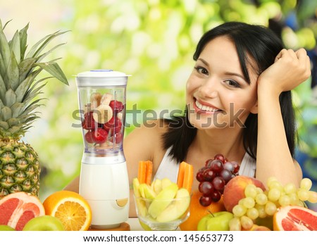 Girl with fresh fruits on natural background - stock photo
