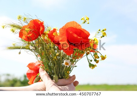 Girl with fresh wildflower bouquet in field - stock photo