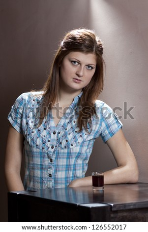 Girl with glass of alcohol sitting on the table - stock photo