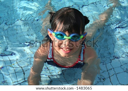 girl with goggle in the pool on sunny day - stock photo