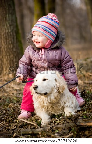Girl with golden retriever are playing in the park - stock photo