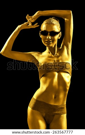 Girl with golden skin in sunglasses. Isolated on black - stock photo