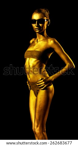 Girl with golden skin in sunglasses. Low key. Isolated on black - stock photo