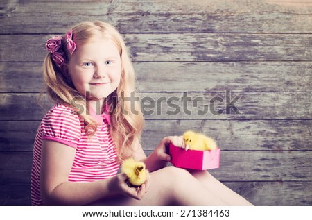 girl with gosling on wooden background - stock photo