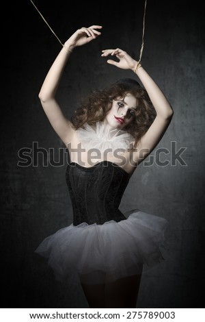 girl with gothic puppet dancer costume and sad clown make-up. She wearing vintage tutu and bowler hat. in marionette pose   - stock photo