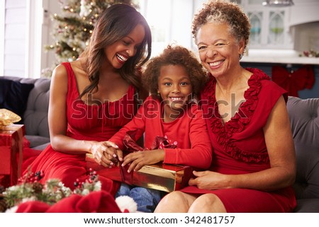 Girl With Grandmother And Mother Opening Christmas Gifts - stock photo
