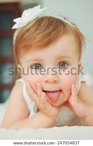 girl with gray eyes showing tongue - stock photo