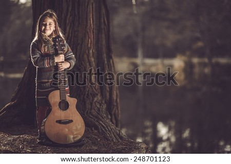 Girl With Guitar in the Park. Little Caucasian Girl with Acoustic Guitar in Hands. Young Guitarist. - stock photo