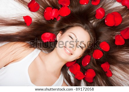 Girl with hair and fluff with rose petals - stock photo