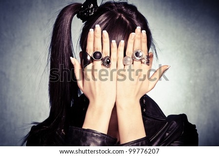 girl with hands full of rings cover her face studio shot - stock photo