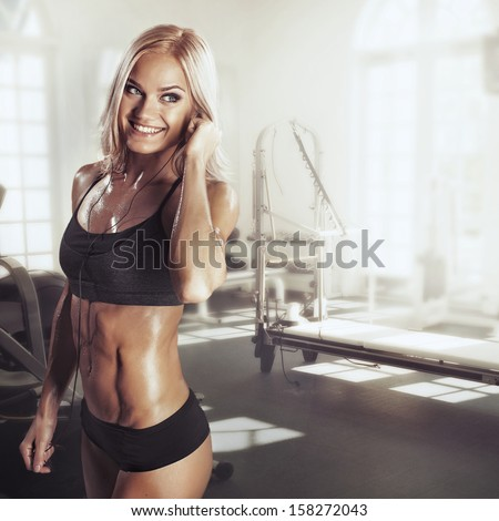 Girl with headphones relaxing in the gym - stock photo