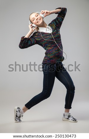 Girl With Headphones Singing and Dancing  leaning back. On grey Background. Full length portrait. - stock photo