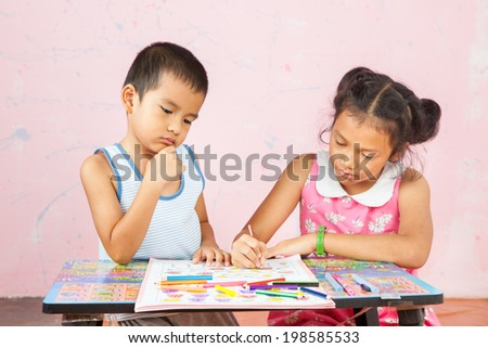 girl with her brother doing school home-work. - stock photo