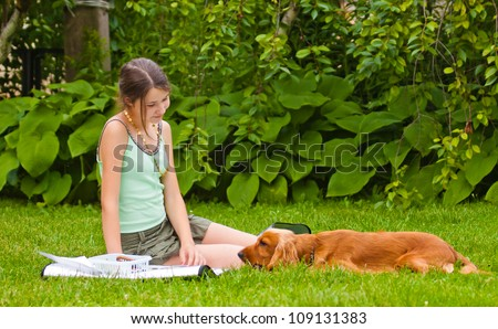 Girl with her dog in the garden - stock photo