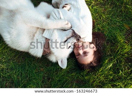 girl with her dog malamut laying on the grass , happy and smiling  - stock photo