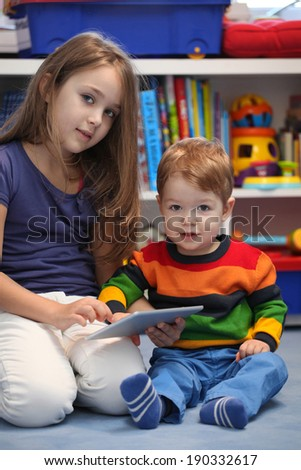 Girl with her little brother fun using a digital tablet computer - stock photo