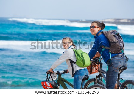 Girl with her mother having a weekend excursion on their bikes on a summer day in beautiful sea landscape - stock photo
