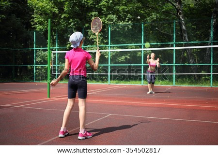 Girl with her mother play tennis on the tennis court, view from the back - stock photo