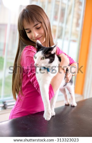 Girl with her restless sick cat trying to calm her down at vet clinic - stock photo