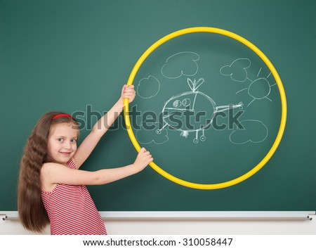 girl with hoop draw helicopter and clouds on board - stock photo