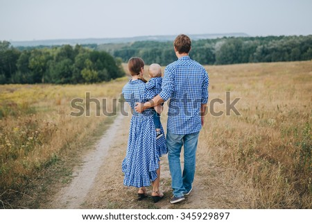 girl with long hair and a blue dress with polka dots, and a guy in a blue dress, holding a child walking along a road in a field at sunset - stock photo