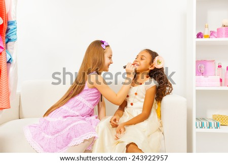 Girl with long hair applies lipstick on her friend - stock photo