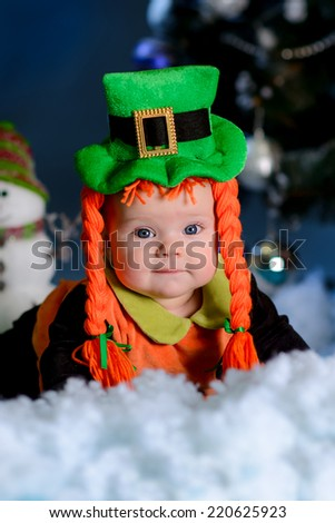 girl with lying on the carpet snow. Christmas tree in the background. smiles elf costume portrait  - stock photo