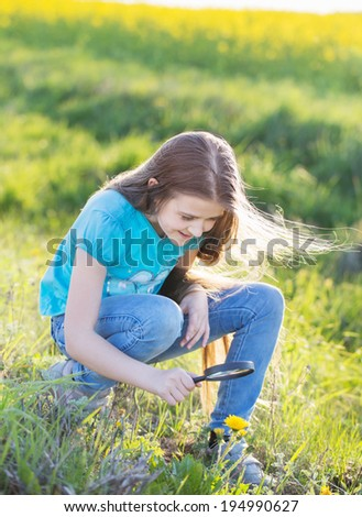 girl with magnifying glass looks at flower - stock photo