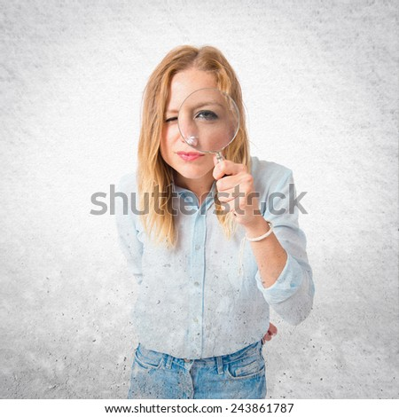 Girl with magnifying glass over textured background - stock photo