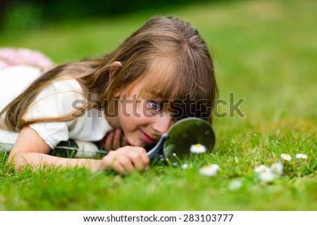 Girl with magnifying glass taking a close look at a flower. - stock photo