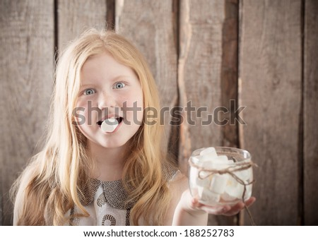 Girl with  marshmallows on wooden background - stock photo