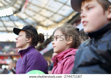 Girl with mother and brother carefully watching game at the stadium - stock photo