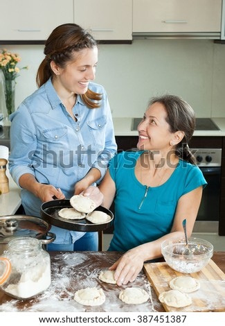 girl with   mother making meat dumplings - stock photo