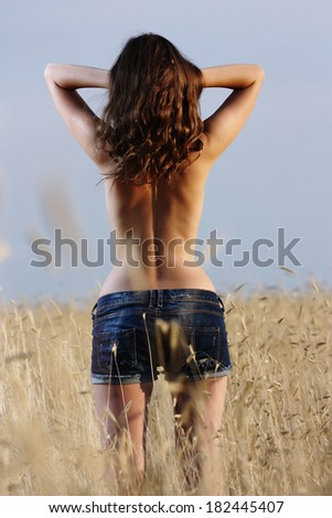 girl with naked back standing in a wheat field - stock photo