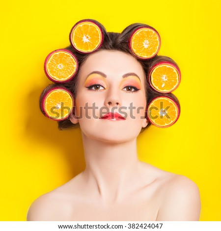 Girl with orange slices in hair curlers on the yellow background - stock photo