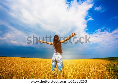 Girl with outstretched arms is enjoys summer day in the field - stock photo