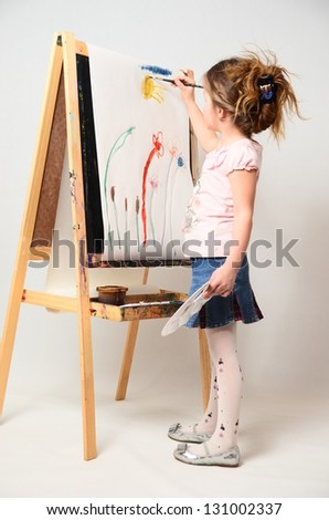 Girl with paint brush near easel, painting flowers on canvas. - stock photo
