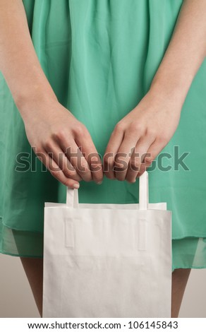 Girl with paper bag. Consumerism symbol. - stock photo