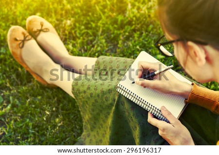 girl with pen writing on notebook on grass outside - stock photo