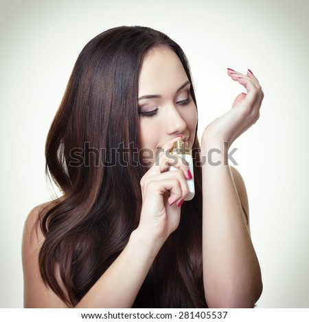 Girl with perfume, young beautiful woman holding bottle of perfume and smelling aroma. Image toned. - stock photo