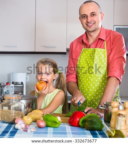 girl with ponytail  helping father to prepare dinner indoors - stock photo