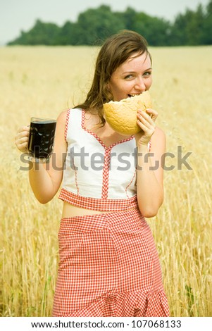 Girl  with quass and bread  at wheat field - stock photo