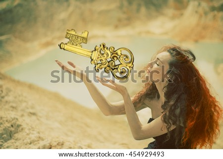 girl with red hair. Cute curly redhead woman with hand near face against outdoor background. Redhead witch praying to Satan with closed eyes. female giving an old key - stock photo